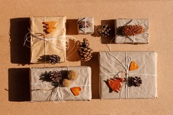 Zero waste Christmas knolling flat lay with hard shadows. Hand crafted eco gift, natural New Year jute decorations top view. Kraft paper wrapping without plastic concept. Orange zest tree,hearts,cones
