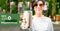 Zero waste concept, A young beautiful asian woman holding a reusable stainless steel tumbler cup with green typography design say