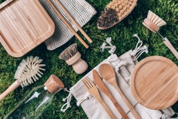 Zero waste concept. Cotton bag, bamboo cultery, glass jar, bamboo kitchen brushes, straws on green moss background. Top view. Copy space. Sustainable zero waste kitchenware utensils and eco dishware.