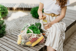 Zero waste concept with copy space. Woman holding cotton shopper and reusable mesh shopping bags with vegetables, products. Eco friendly mesh shopper. Zero waste, plastic free concept