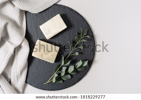 Zero waste cosmetics concept. Flat lay, top view of natural, organic solid handmade soap and eucalyptus plant near towel on black plate stand against white copy space background