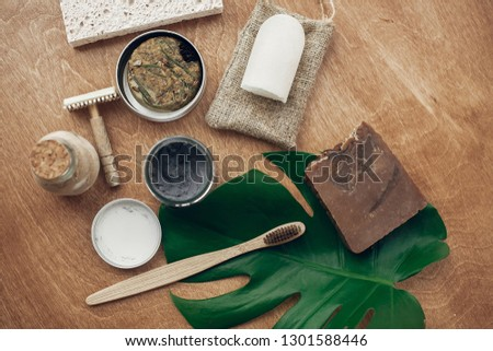 Zero waste flat lay. Natural soap, solid shampoo, metal razor, crystal deodorant, charcoal toothpaste, sponge, bamboo toothbrush, ubtan on wood with green monstera leaf. Sustainable lifestyle