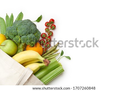 Zero waste food shopping with reusable bags. Flat lay with fruits and vegetables in textile tote bag isolated on white background with copyspace.