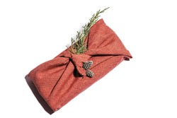 Zero waste gift wrapping traditional Japanese furoshiki style. Hand made gift package for Christmas with fabric thuja and cones isolated on white. Ecological concept eco-friendly decor xmas