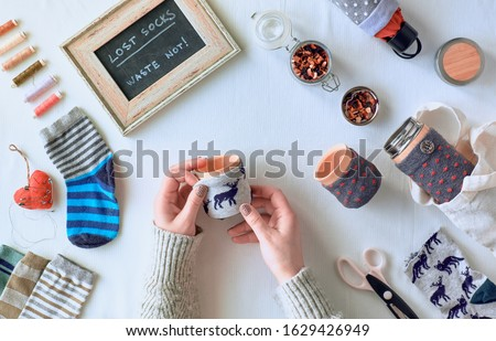 Zero waste household. Making bamboo cup and thermos can sleeve out of stray socks. Upcycle of single mismatched socks. Flat lay on textile tablecloth. Low impact life, upcycling socks to cup sleeves.