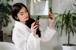 Zero waste lifestyle concept. Minded young adult woman in bathrobe, spending morning at bathroom, choosing personal hygiene items, holding glass bottle with cosmetic care product