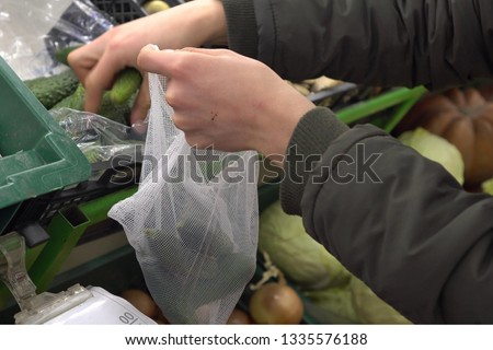 Zero Waste Reusable Produce Bag. A young man buys vegetables in a supermarket