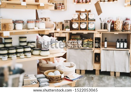 Zero waste shop interior details. Wooden shelves with different food goods and personal hygiene or cosmetics products in plastic free grocery store. Eco-friendly shopping at local small businesses