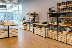 Zero waste shop interior. Wooden shelves with different food goods and personal hygiene or cosmetics products in plastic free grocery store. Eco-friendly shopping at local small businesses