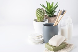Zero waste, sustainable bathroom and lifestyle. Bamboo toothbrush, natural soap bar, loofah sponge, cotton pads, homemade DIY beauty products in reusable bottles over white background.