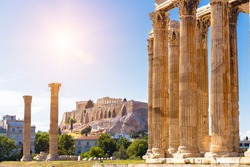Zeus temple overlooking Acropolis, Athens, Greece. These are famous landmarks of Athens. Sunny view of Ancient Greek ruins, great columns of classical building in Athens city center. Travel concept.