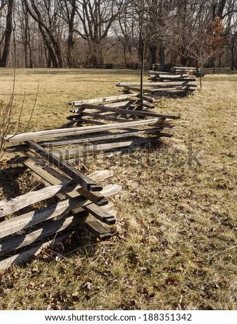zig zag split rail fence crossing a field towards trees