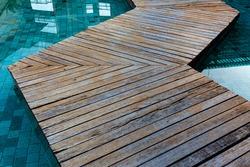 zigzag wooden bridge cross over the swimming pool.  japanese zig-zag walkway on water of pool.