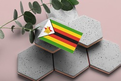 Zimbabwe flag on hexagon stylish stones. Pink copy space background. Flat lay, top view minimal national concept.