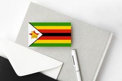 Zimbabwe flag on minimalist letter background. National invitation envelope with white pen and notebook. Communication concept.