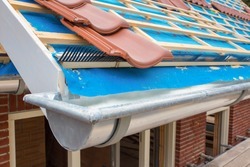 Zinc gutter and roof tiles on new house