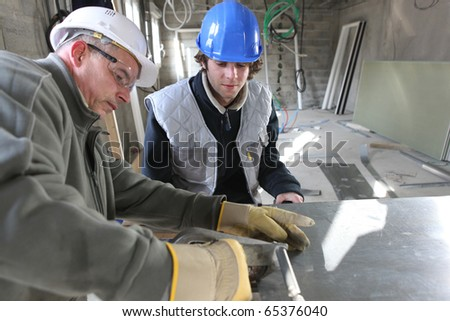 Zinc worker and apprentice in workshop