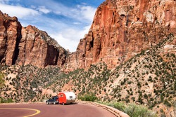 Zion National Park, Utah. Red vintage trailer going down the road. Majestic mountain scenery.