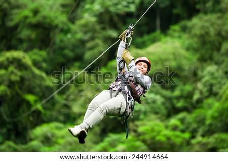 Photo of  zip line zipline wire canopy people normal rope jungle sport climbing grown pioneer wearing casual clothing on zipline trip selective stress against blurred forestry zip line zipline wire canopy peopl