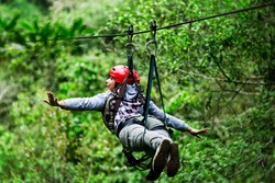 zipline zip line canopy wire forest jungle woman safety back adult tourist wearing casual clothing on zipline trip selective focus against blurred forest zipline zip line canopy wire forest jungle wom