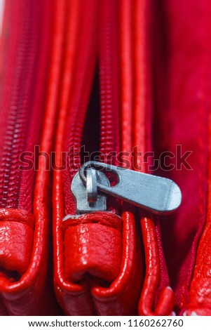 zipper close-up on a bright red female clutch. Handbag details. macro photo. fashion, style, beauty, decoration, decoration, things #1160262760
