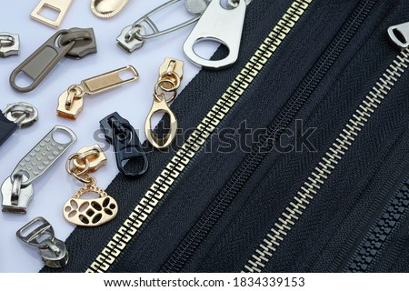 Photo of  Zipper on a black fabric base with different color runners. different types of metal zipper slider for zipper. Gold, silver chrome runners  for sewing clothes with a zipper