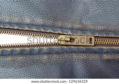Zipper on brown leather motorcycle jacket.