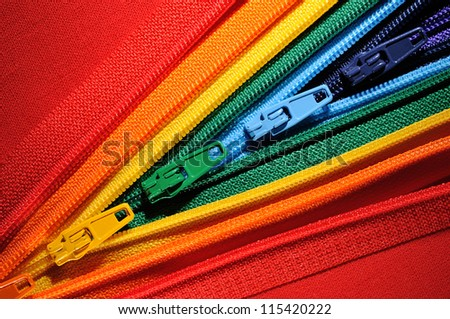 Zippers lined in a row on the fabric in the manner of the rainbow