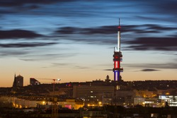 Zizkov television tower illuminated with the colors of czech flag at sunrise, Prague, Czech Republic