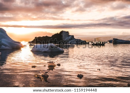 Zodiac boat sailing in Glacier lagoon Jokulsarlon sunset between icebergs pieces of ice clouds sky reflecting on the water in Iceland #1159194448