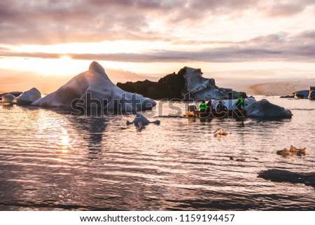 Zodiac boat sailing in Glacier lagoon Jokulsarlon sunset between icebergs pieces of ice clouds sky reflecting on the water in Iceland #1159194457