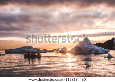 Zodiac boat sailing in Glacier lagoon Jokulsarlon sunset between icebergs pieces of ice clouds sky reflecting on the water in Iceland #1159194460