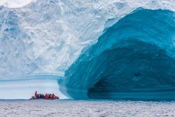 Zodiac in front of enormous ice berg in Antarctica