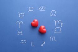 Zodiac signs and red hearts on color background. Love horoscope concept