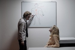 Zombie businessman looking at female colleague while pointing at whiteboard with drawing of human