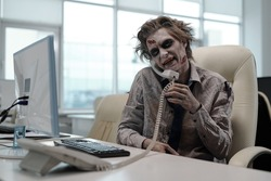 Zombie businessman with phone receiver between his shoulder and cheek looking at computer screen