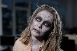 Zombie female standing in front of camera in dark room or office