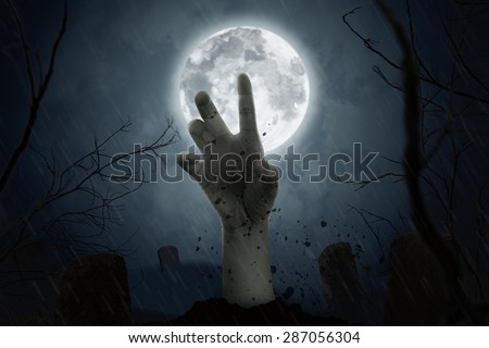 zombie hand coming out of his grave in full moon night. #287056304