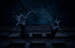 Zombie hand rising out from old ancient window castle building over dead tree, full moon and cloudy spooky sky, Halloween mystery concept