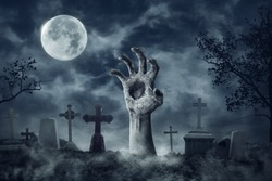 Zombie Hand Rising Out Of A Graveyard cemetery In Spooky dark Night full moon. Holiday event halloween concept.