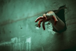 Zombie hand through the cracked wall. Horror and scary film concept. Halloween day theme. Green tone like ghost movie