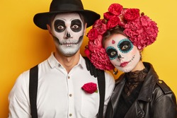 Zombie portrait. Dead woman and man wears skull makeup, painted for Halloween, look at camera surprisingly, dressed in black and white outfit for All Saint Day, isolated over yellow background.