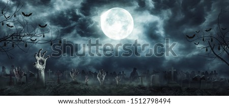 Zombie Rising and hands Out Of A Graveyard cemetery scary In Spooky dark Night full moon. Holiday event halloween concept. Сток-фото ©