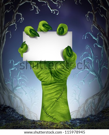 Zombie rising hand holding a blank sign card as a spooky halloween or scary symbol with textured green monster skin in a foggy night tree forest background as a cemetery like creepy place.