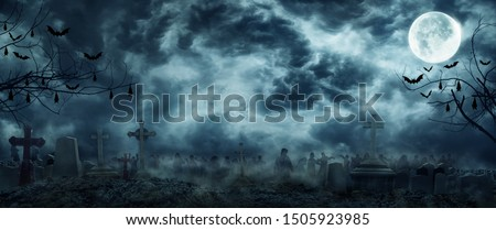 Zombie Rising Out Of A Graveyard cemetery In Spooky scary dark Night full moon bats on tree. Holiday event halloween banner background concept.