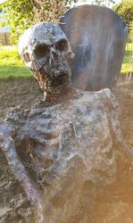 Zombie skeleton sitting in front of a halloween tombstone