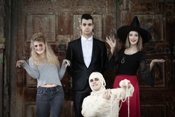 Zombie, vampire, witch and mummy standing in front of the door of the haunted house