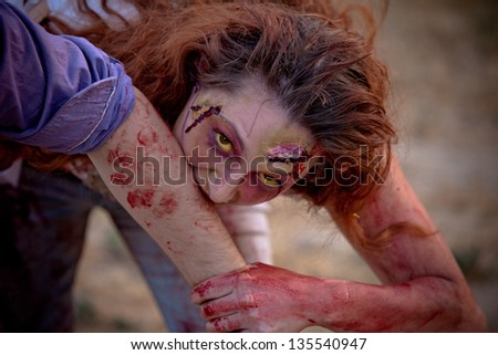Zombie woman outside with yellow eyes looking at camera biting a victim