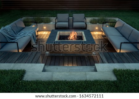 Zone for relax with a wooden floor and a tiled stair outdoors. There is a burning fire pit, gray sofas and armchairs, plaid, luminous lamps. Horizontal.