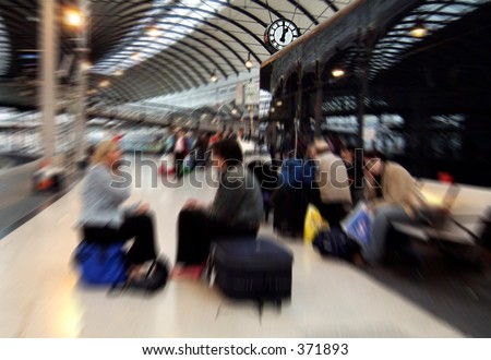 Zoom blurred image of people waiting for trains on Newcastle-upon-Tyne central station, UK, the zoom centred on station clock showing one o\'clock 13.00 hrs